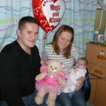Braveheart Anna May getting cuddles from Mummy, Daddy & Princess bear