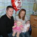 Braveheart Anna May getting cuddles from Mummy, Daddy & Princess bear