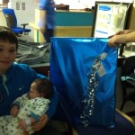Braveheart Zachary  getting hugs from his big brother before opening his gift